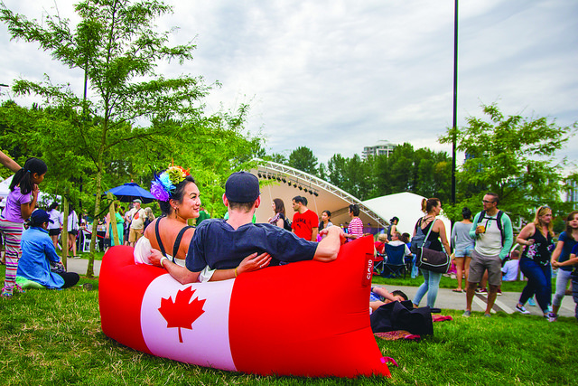 Coquitlam Canada Day - Town Centre Park Two People Sitting on an Inflatable Pillow Chair Featuring the Canada Flag
